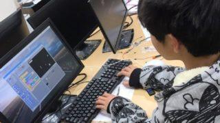 シューティングゲームをプログラミングしている中学生の男の子