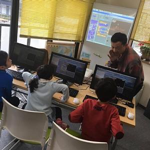 無料体験授業でシューティングゲームを夢中で作っている3人の小学生の子どもたち
