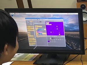 スクラッチでシューティングゲームを作っている小学生の男の子
