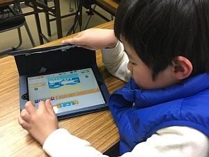 iPadで、Scratch Jrを使って、プログラミングをしている男の子