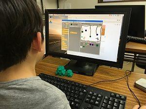 Scratchでゲームのプログラミングをしている小学生の男の子