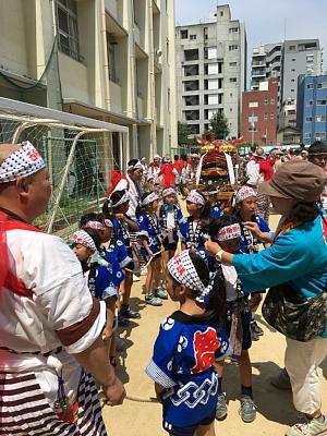 御霊神社の夏祭りの獅子講の大獅子とそれを引っ張る子どもたち。出発前の西船場小学校の校庭にて