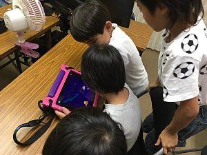 iPadで自分たちで作ったゲームをみんなで遊び合っているジュニアコースの子どもたち