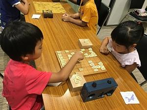 第2回将棋デーinプログラミング教室で熱心に対局をしている小学生の男の子と女の子