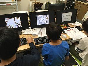 プログラミング教室で、互いにプログラミングしたダンジョンゲームを遊んでいる3人の小学生の男の子