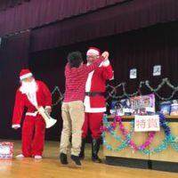 西船場小学校のクリスマス会で、クジ引きの特賞が当たってサンタさんとハイタッチをする小学生の男の子