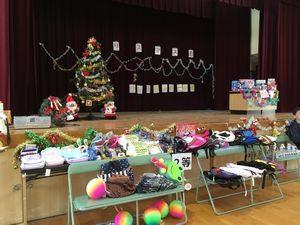 西船場小学校のクリスマス会の舞台の様子。クリスマスツリーにクジ引きの景品が所狭しと置かれています