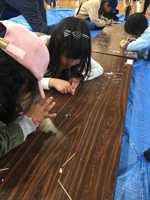 西船場小学校のクリスマス会で、型抜きに熱中してチャレンジしている小学生の子供たちの様子