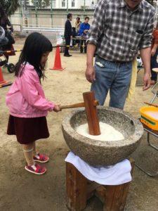西船場もちつき大会でおもちをついている幼稚園の女の子(2017)
